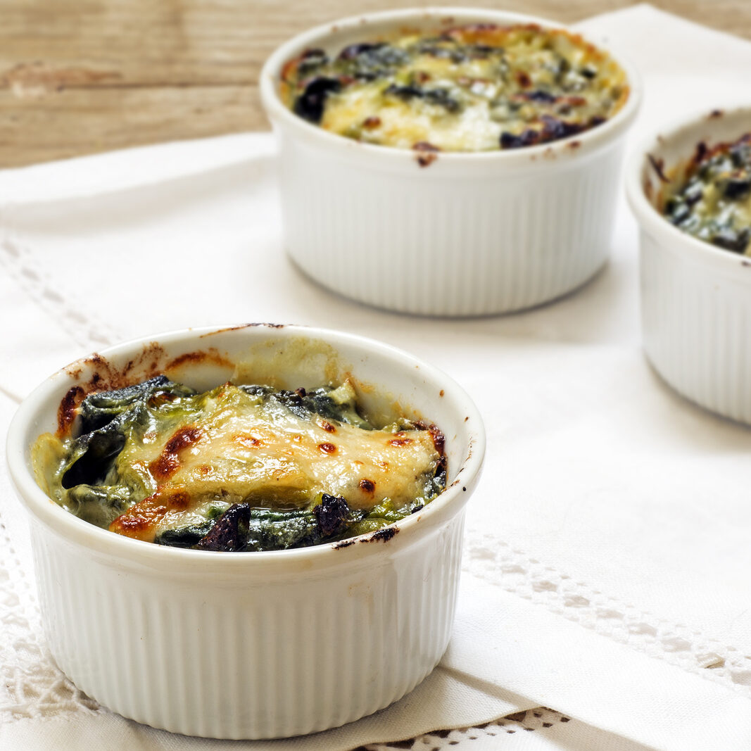 baked spinach with cheese in small casserole servings white napkin on a rustic wooden table selected focus narrow depth of field